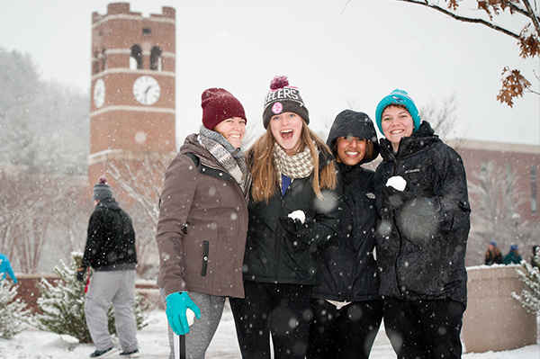 Students in the snow in front of the alumni tower