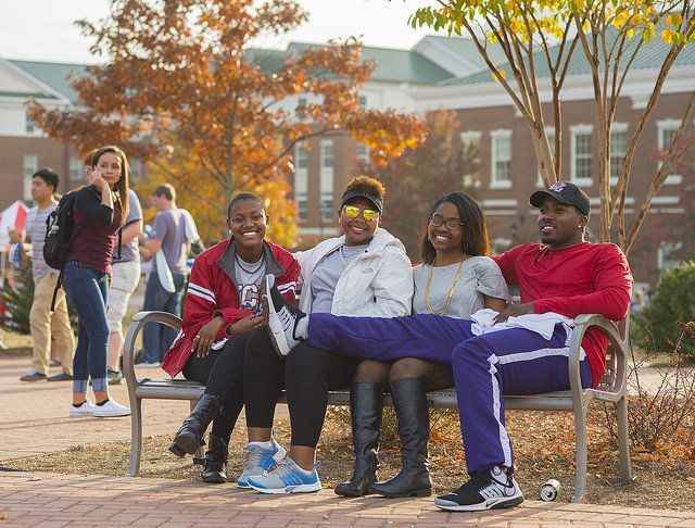 Students sit outside on a fall day.